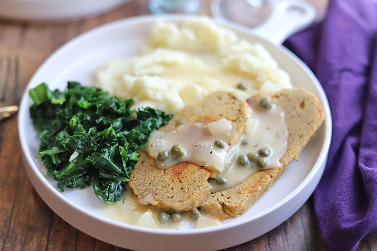 Browned seitan slices on plate with lemon piccata sauce, kale, and mashed potatoes.