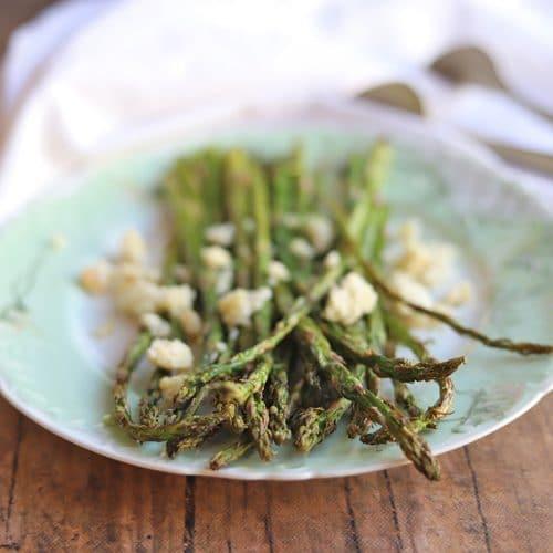 Asparagus stalks covered in vegan feta cheese on plate.