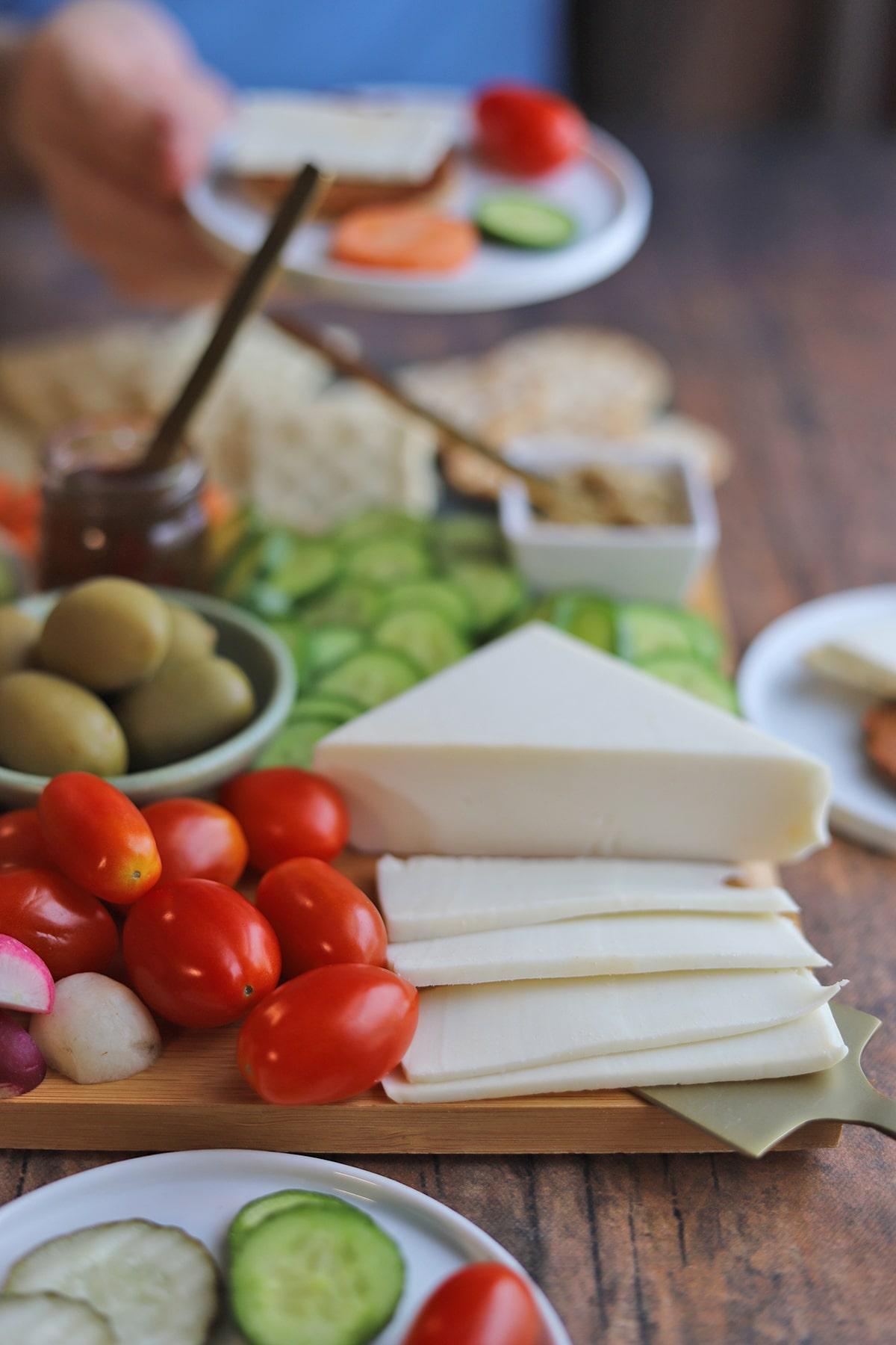 Slices of vegan Swiss cheese on cheeseboard.