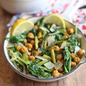 Roasted asparagus in skillet with chickpeas and spinach.