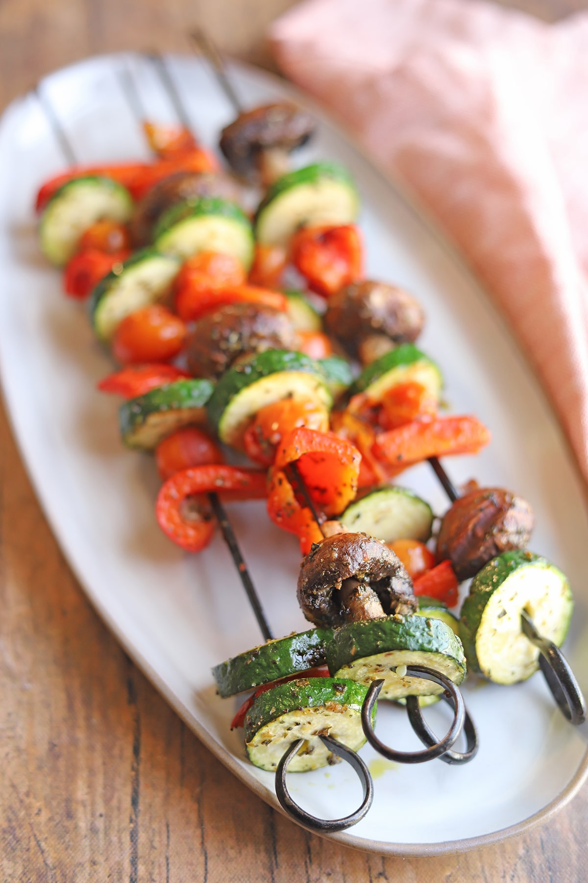 Zucchini, bell peppers, mushrooms, and tomatoes grilled on skewers.