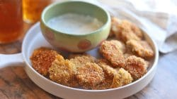 Beer battered pickles on plate with ranch dip.