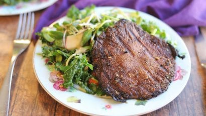 Grilled mushroom cap on plate with salad.