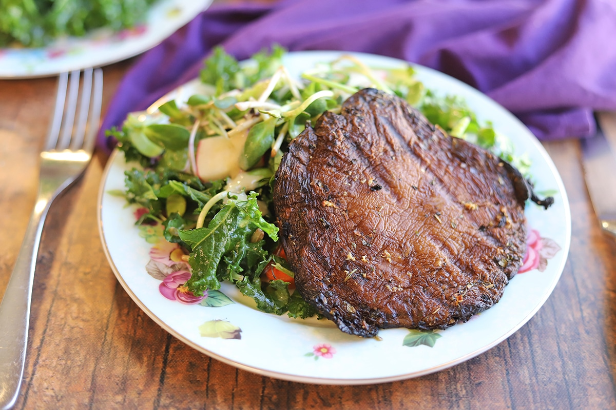 Grilled Portobello mushroom cap on plate with salad.
