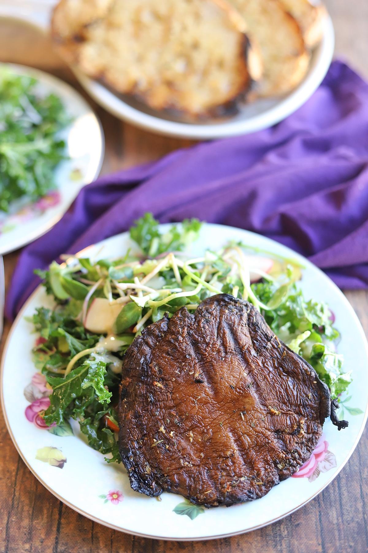 Grilled portobello mushroom on plate with kale salad.