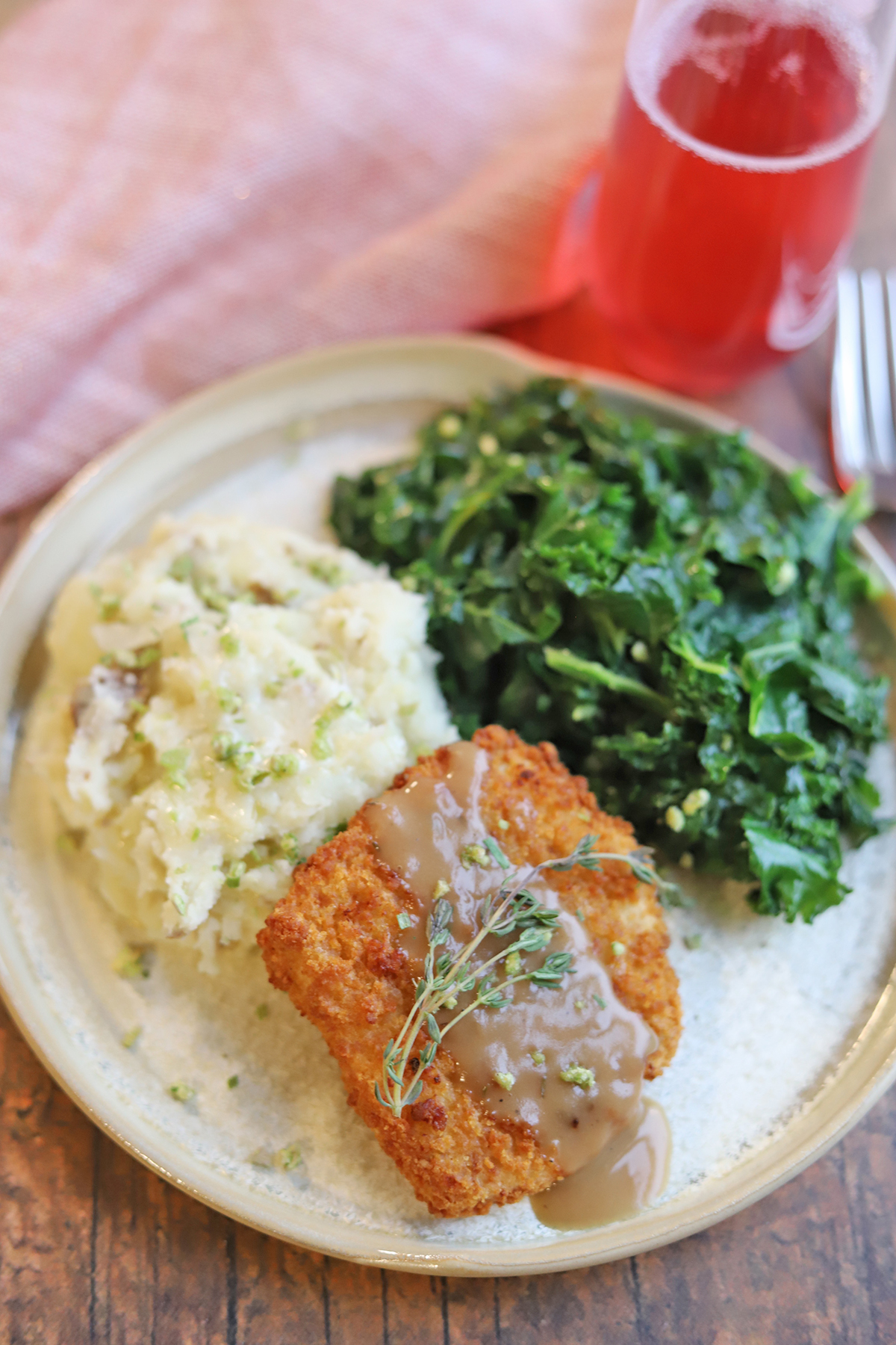 Mashed potatoes on plate with greens and Gardein turk'y cutlets.