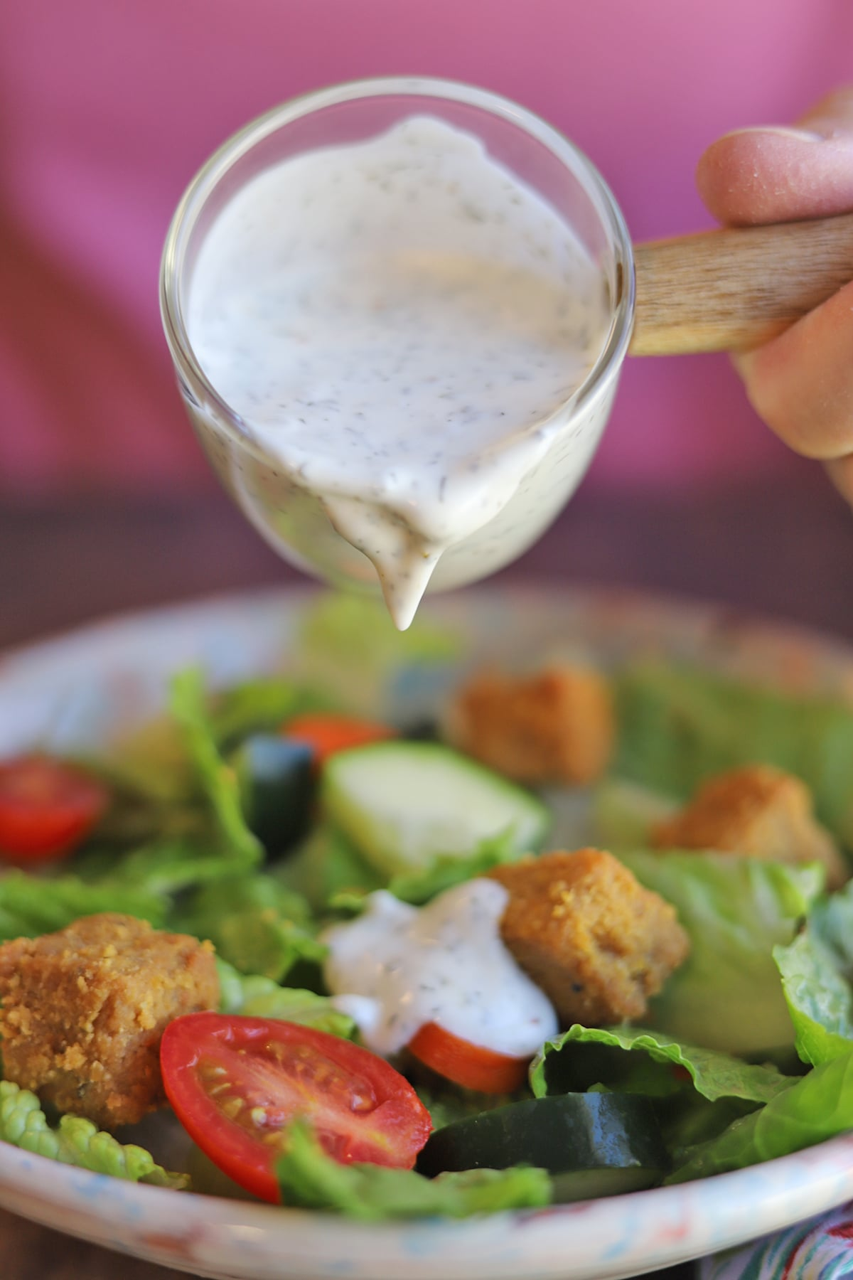 Dressing being poured over salad.