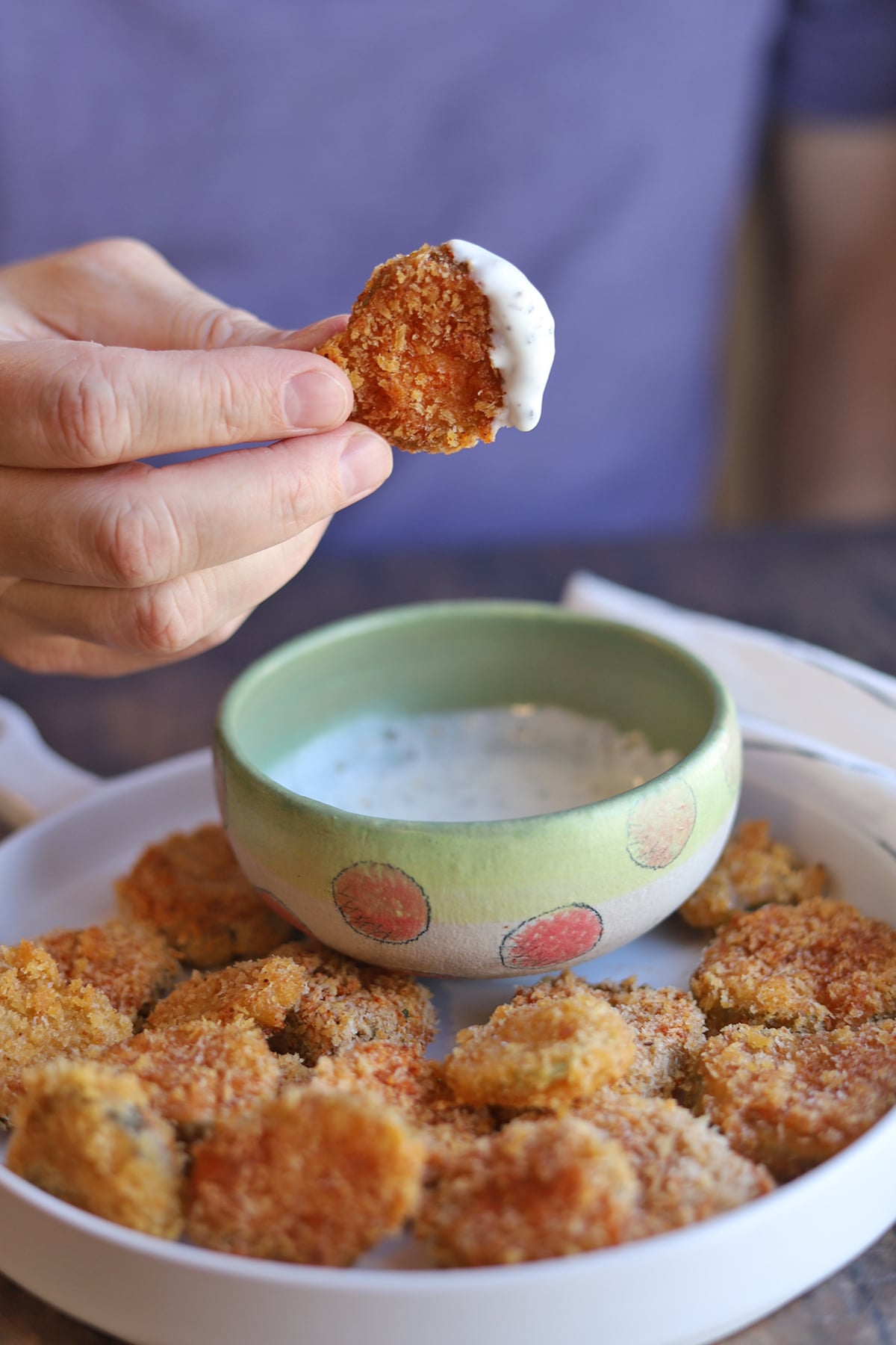 Fried pickle chip being dipped into ranch sauce.
