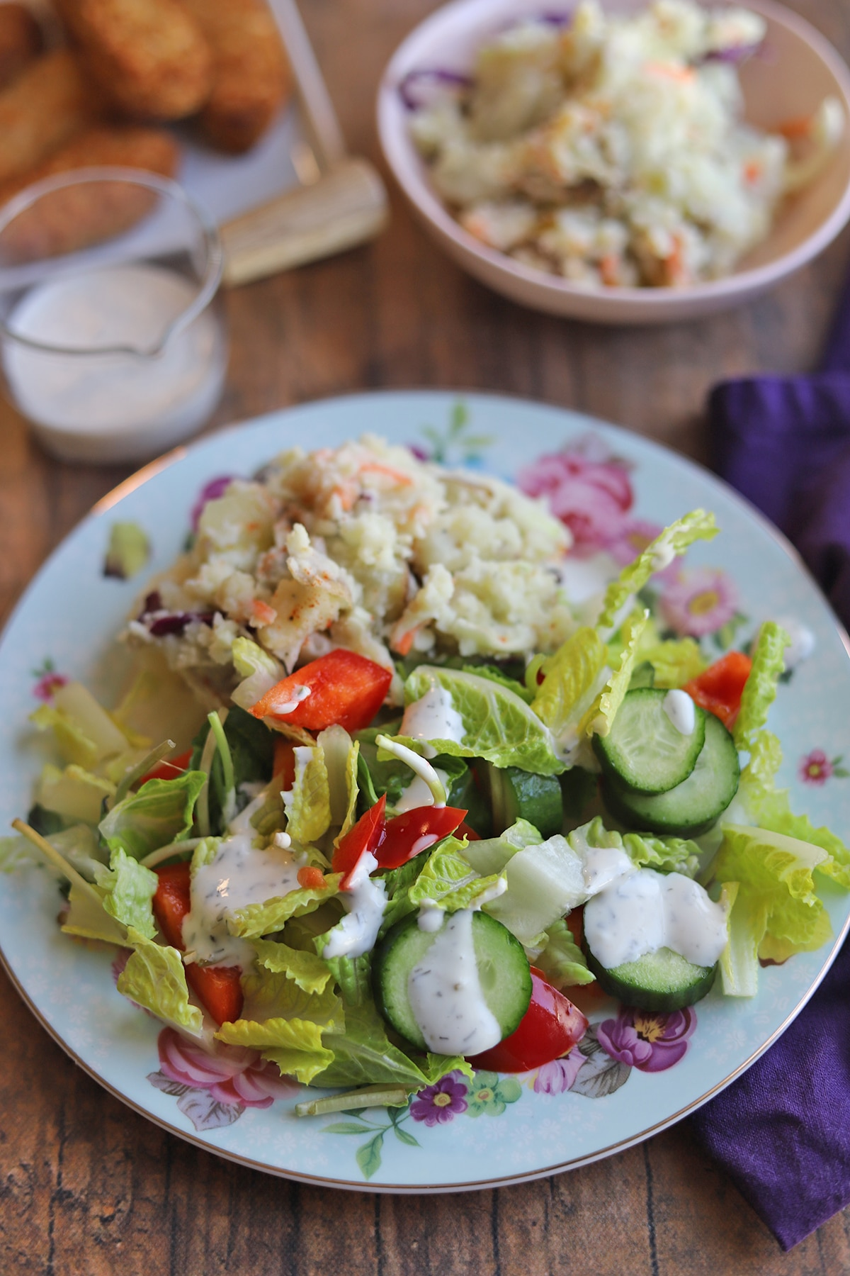 Salad topped with ranch dressing on flowered plate.