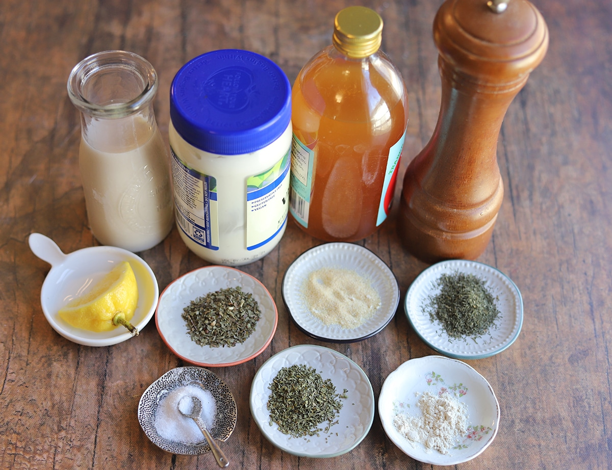 Ingredients for vegan ranch dressing: Mayo, non-dairy milk, apple cider vinegar, lemon, and spices.
