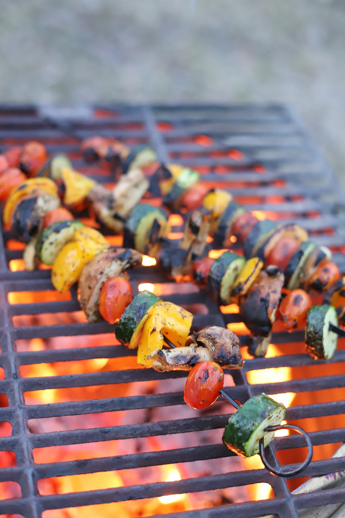Vegetable skewers cooking on fire pit.