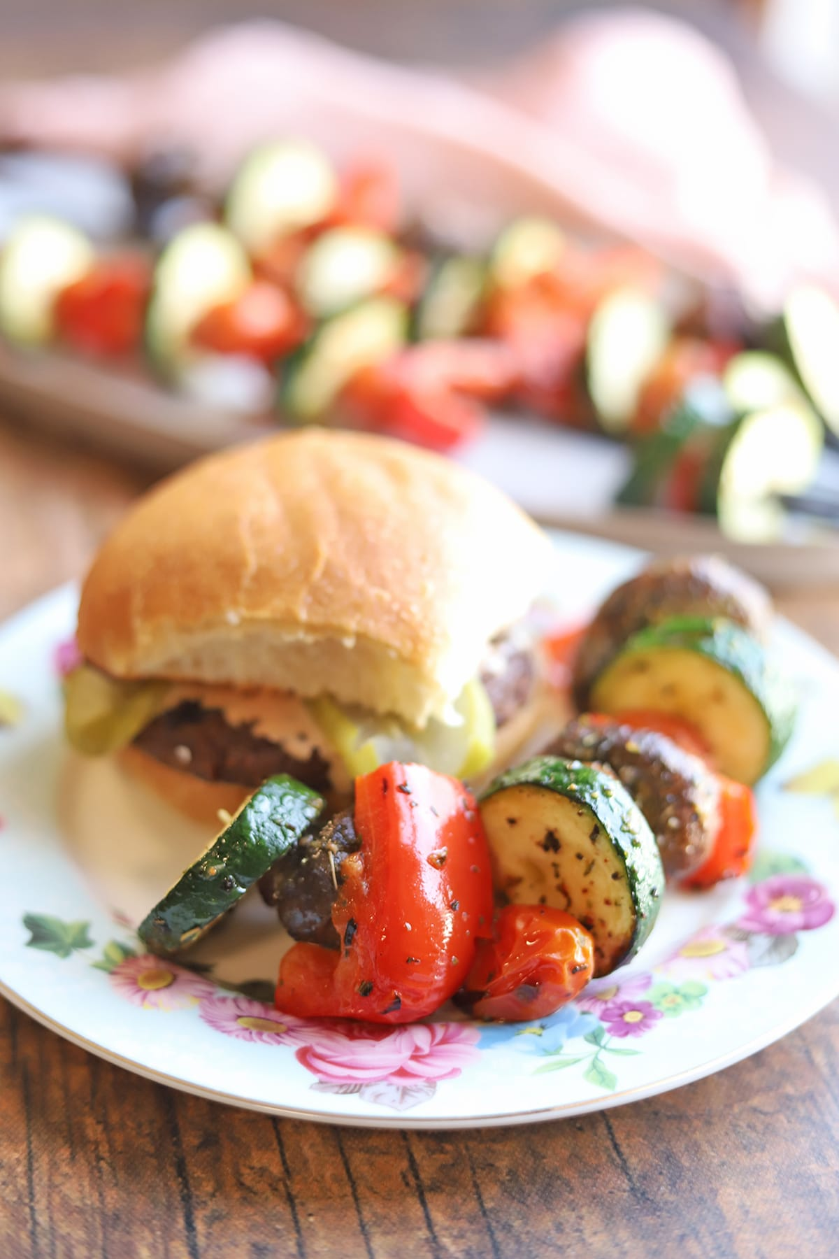 Burger on plate with grilled vegetables.