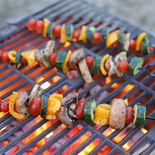 Vegetable skewers over fire pit with grate.