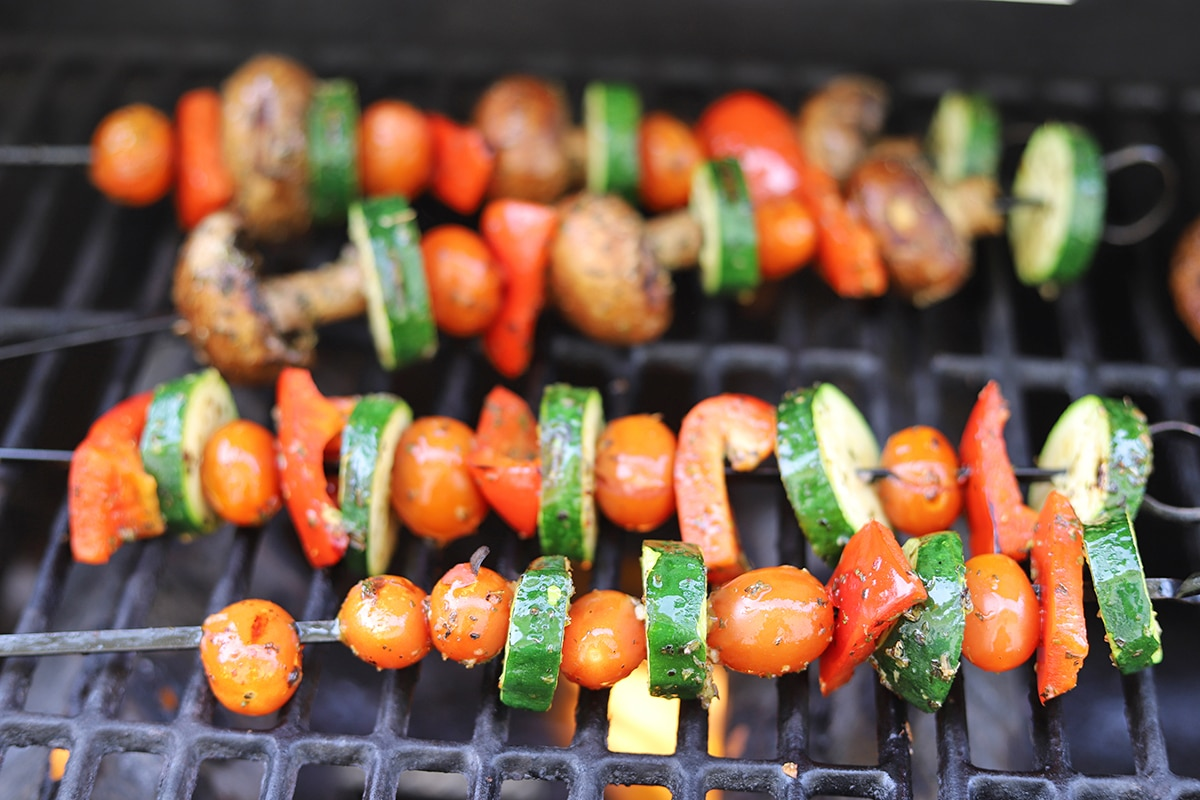 Vegetable kebabs cooking on an outdoor grill.