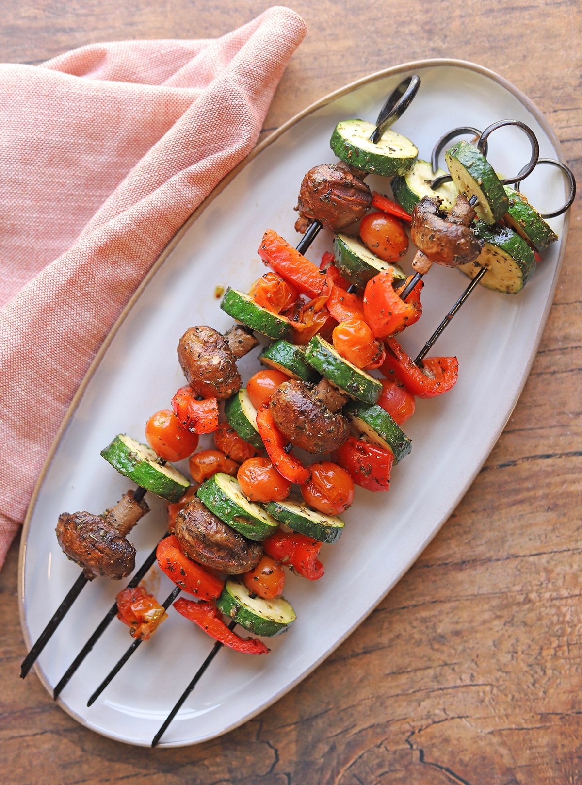 Grilled vegetable skewers on platter with napkin.