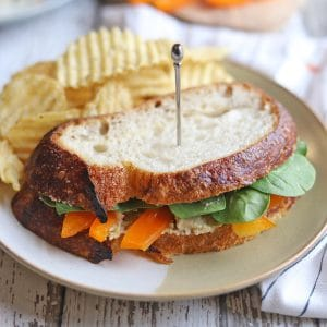 Vegetable sandwich with jalapeno cashew cheese on plate.