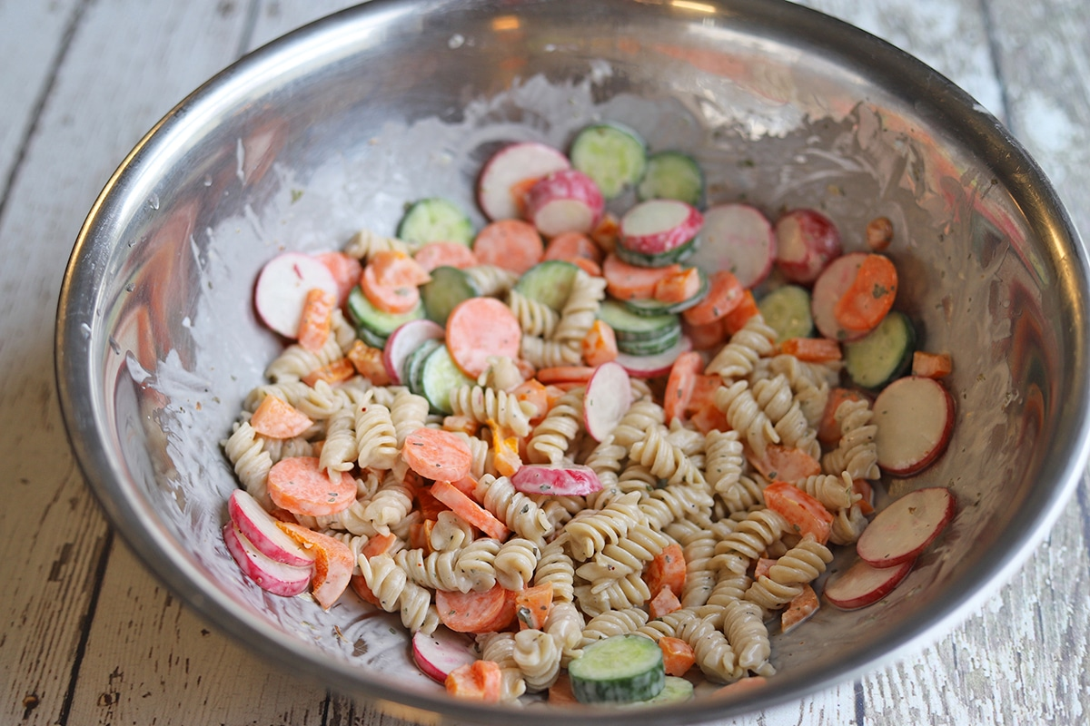 Pasta being mixed in bowl with sliced vegetables and mayo dressing.