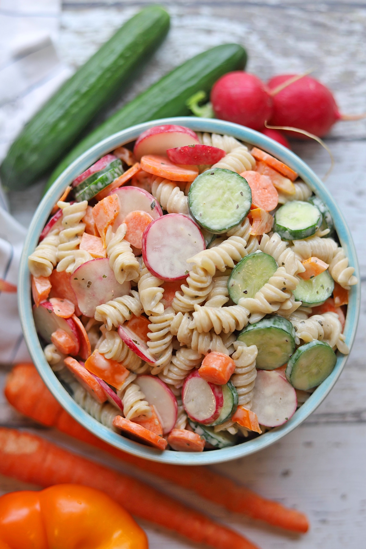 Overhead vegan pasta salad with sliced cucumbers, carrots, and radishes.