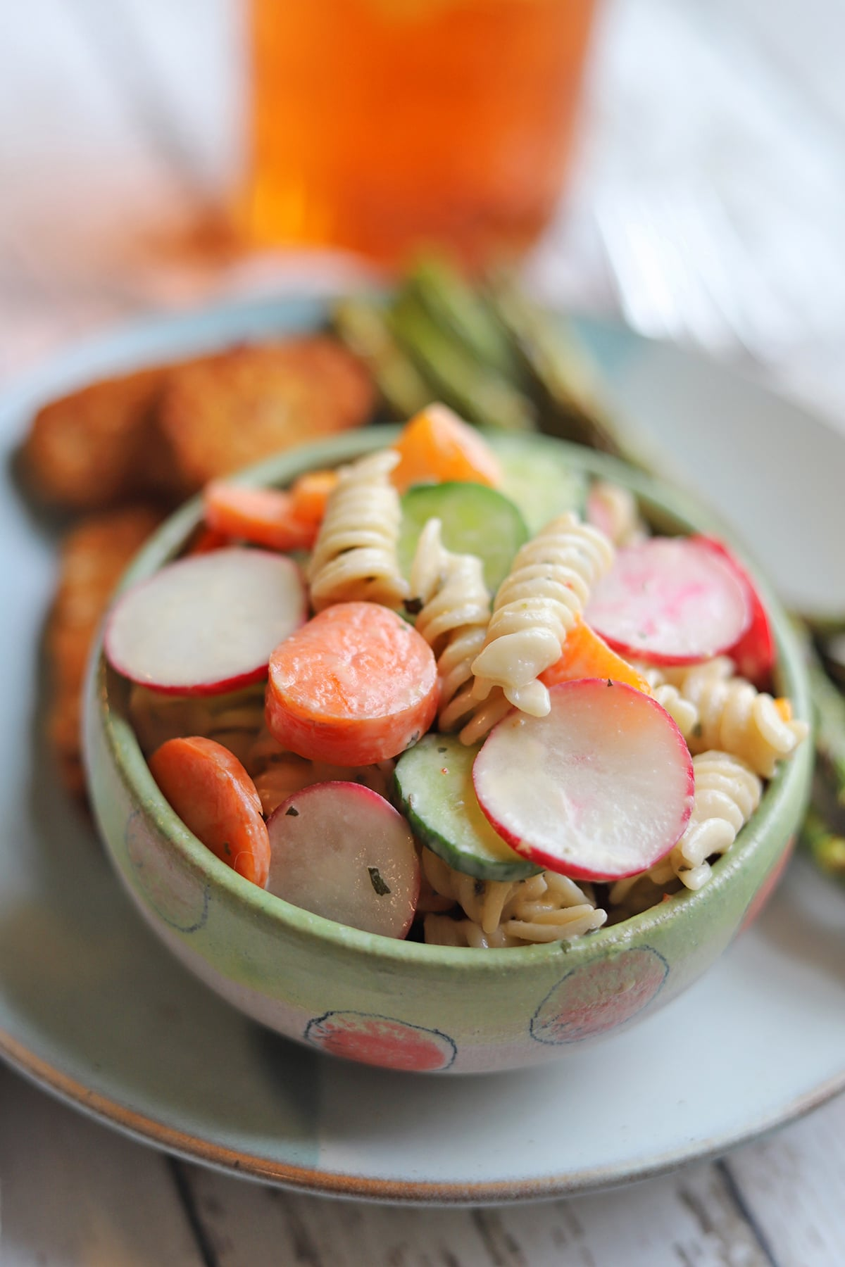 Close-up bowl of pasta salad by vegan chick'n strips and asparagus.