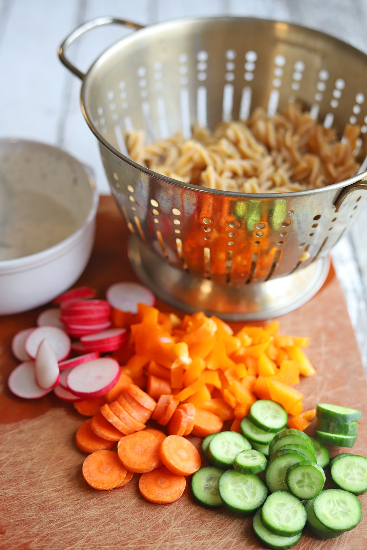 Sliced vegetables on table by mayo dressing and pasta in colander.