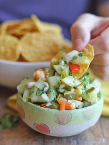 Chip dipping into pickle salsa.