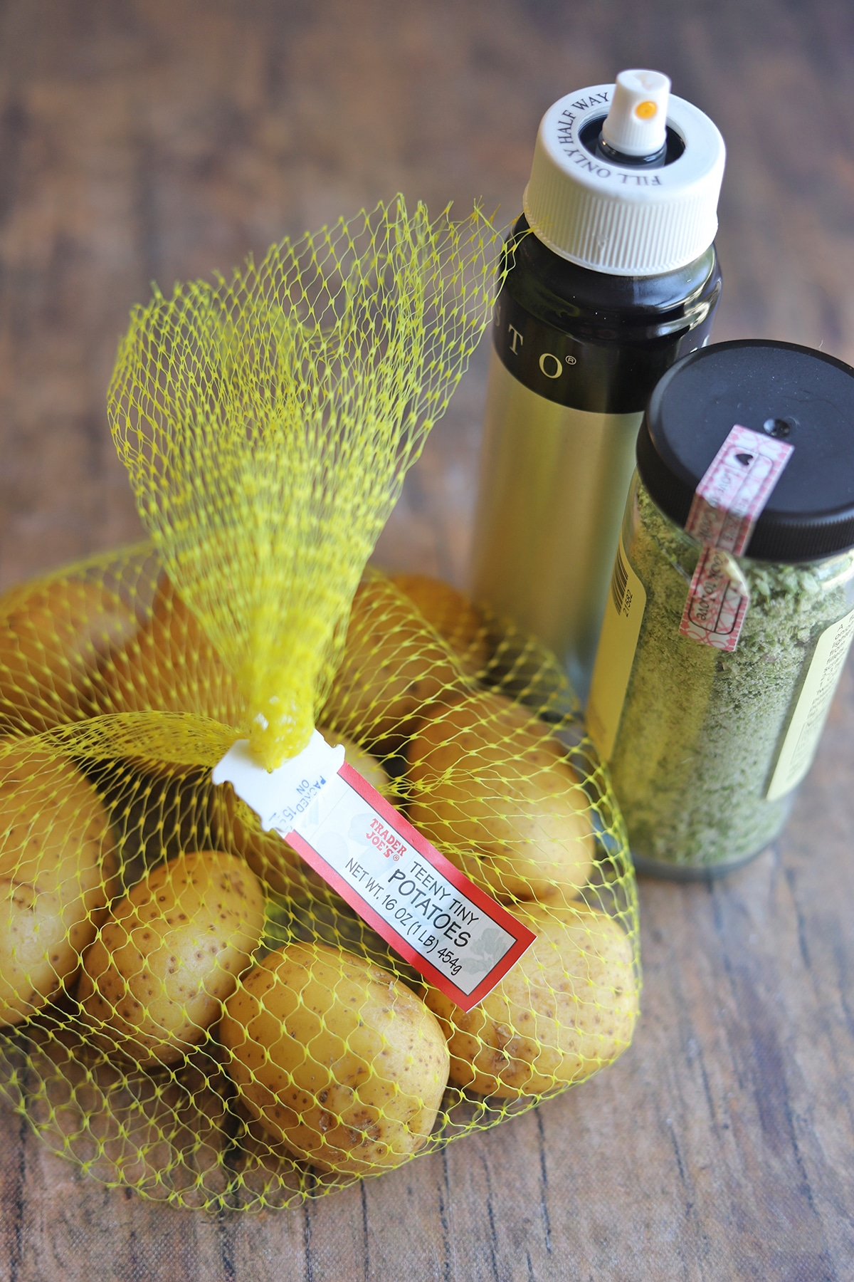 Baby potatoes in bag by seasoning and oil spray.