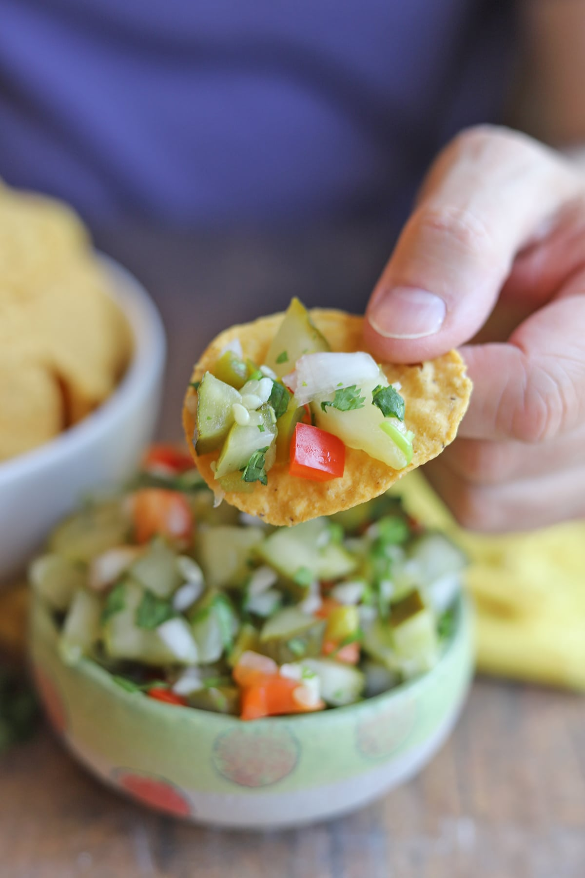 Hand holding tortilla chip with pickle salsa.