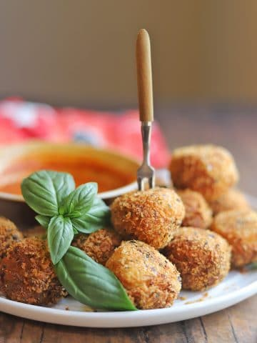 Platter with fried cheese balls & tiny fork.