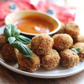 Platter of fried almond cheese balls with basil & marinara dipping sauce.