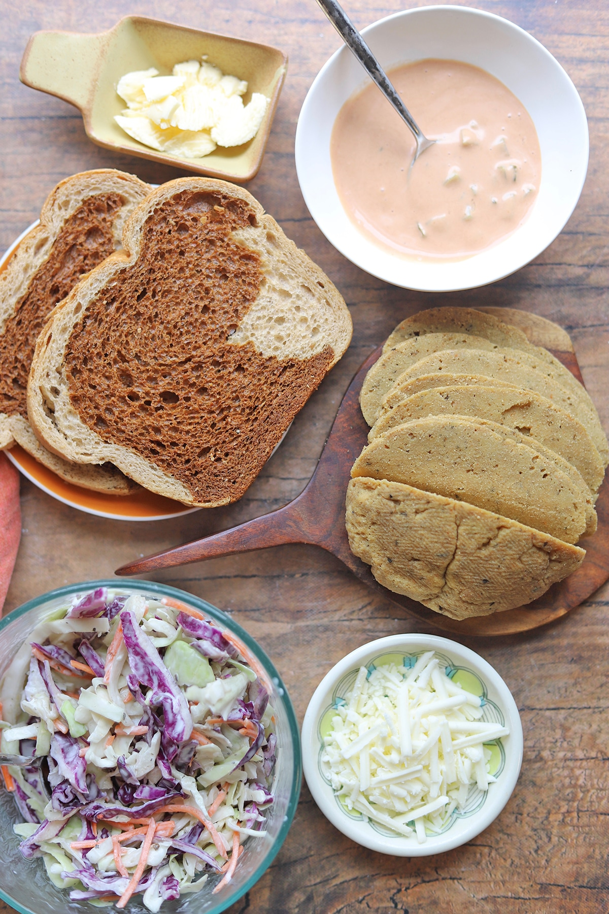 Overhead table with rye bread, Thousand Island dressing, butter, coleslaw, seitan, and shredded cheese.