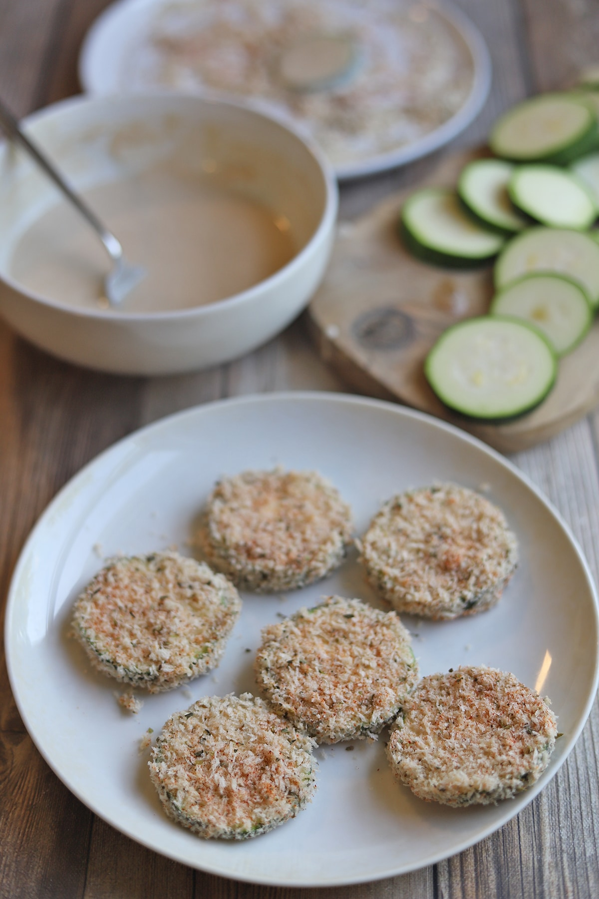 Zucchini slices coated in breadcrumbs in breading station.