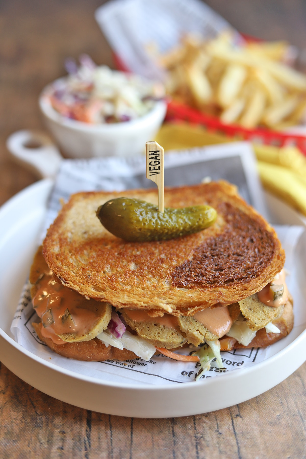 Toasted Rachel sandwich with seitan chicken on plate and topped with a pickle.