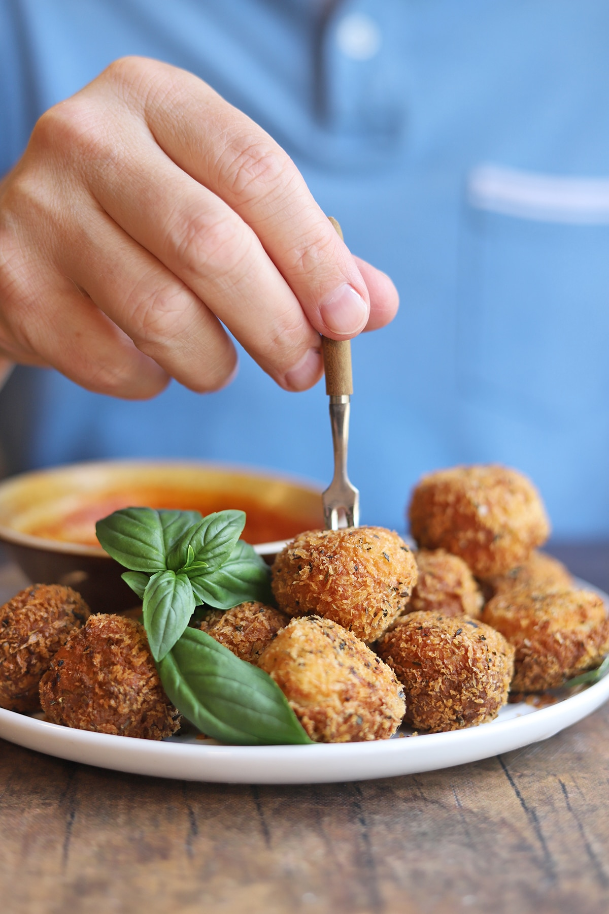 Hand spearing fried vegan cheese ball with tiny fork.