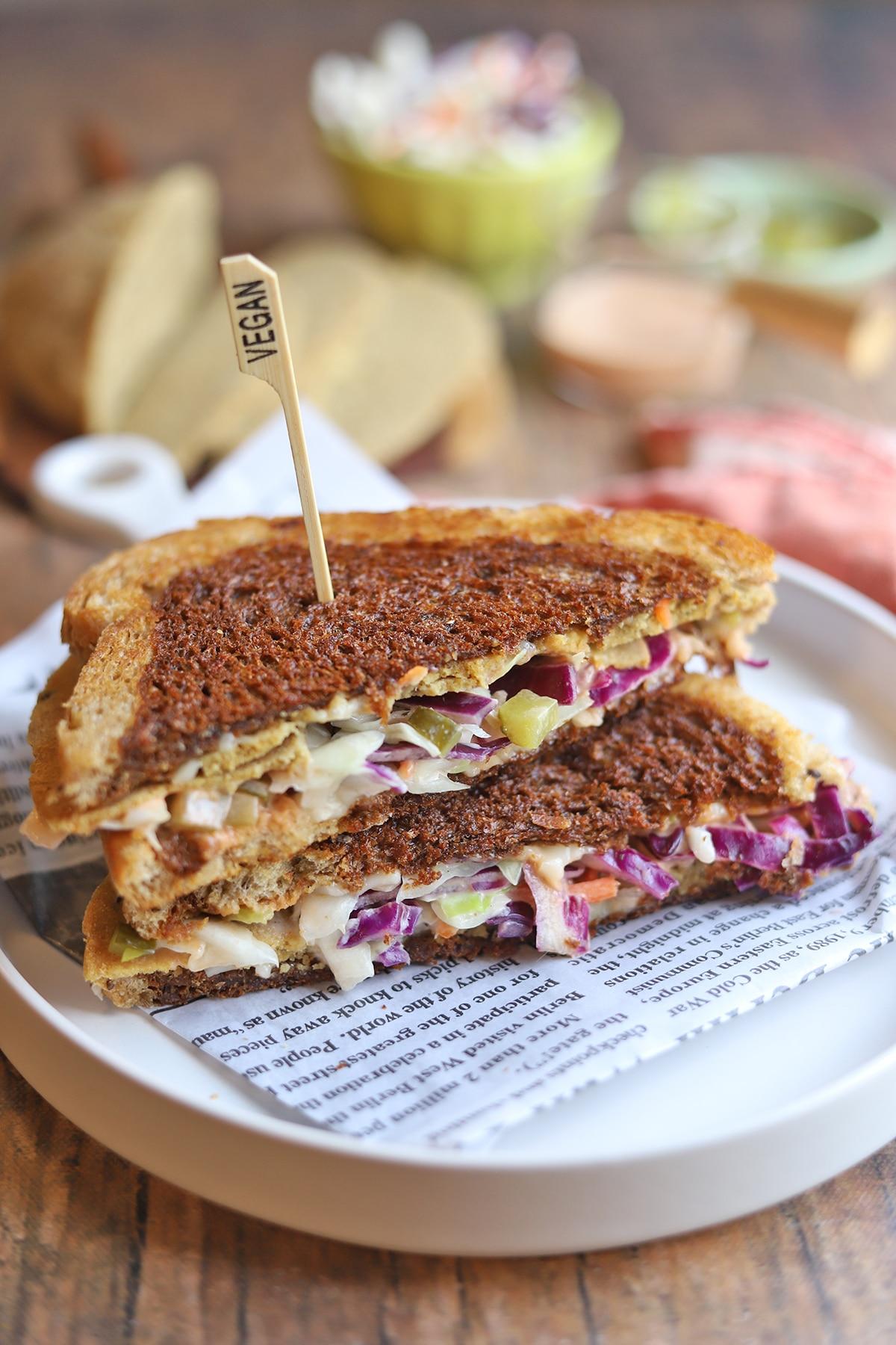 Sliced toasted Rachel sandwich on plate.