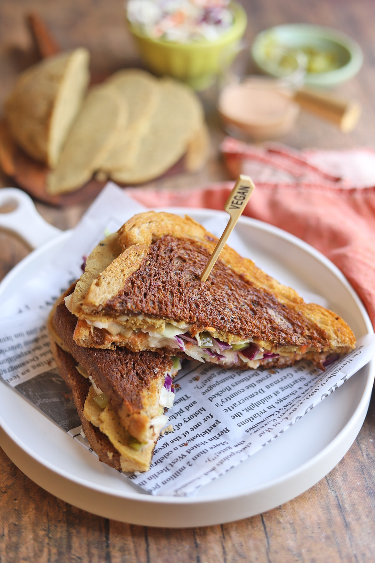 Toasted sandwich on plate with seitan and coleslaw.