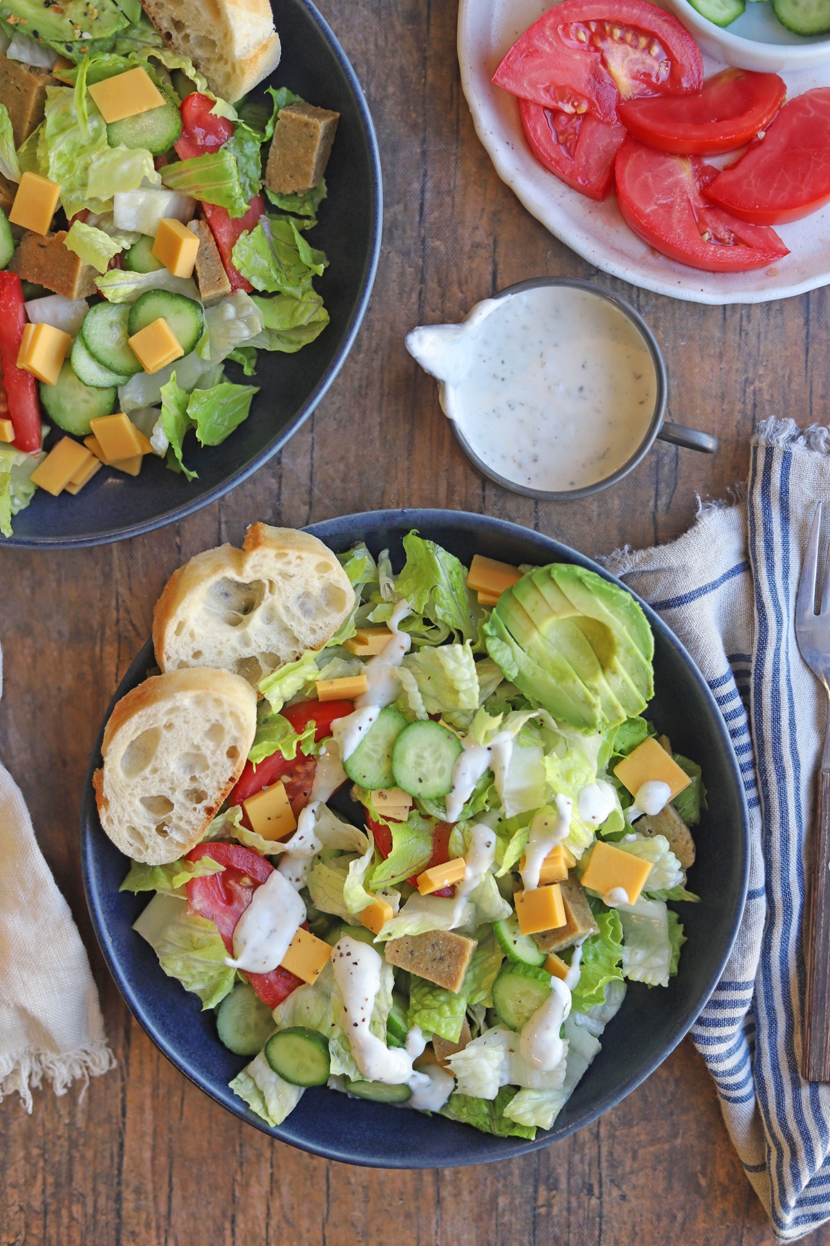 Overhead chef salads in bowl by dressing.
