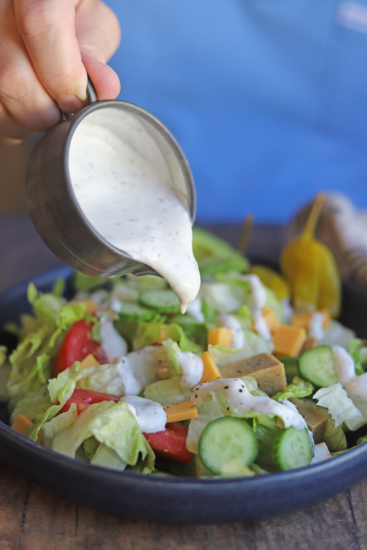 Hand pouring dressing onto salad.