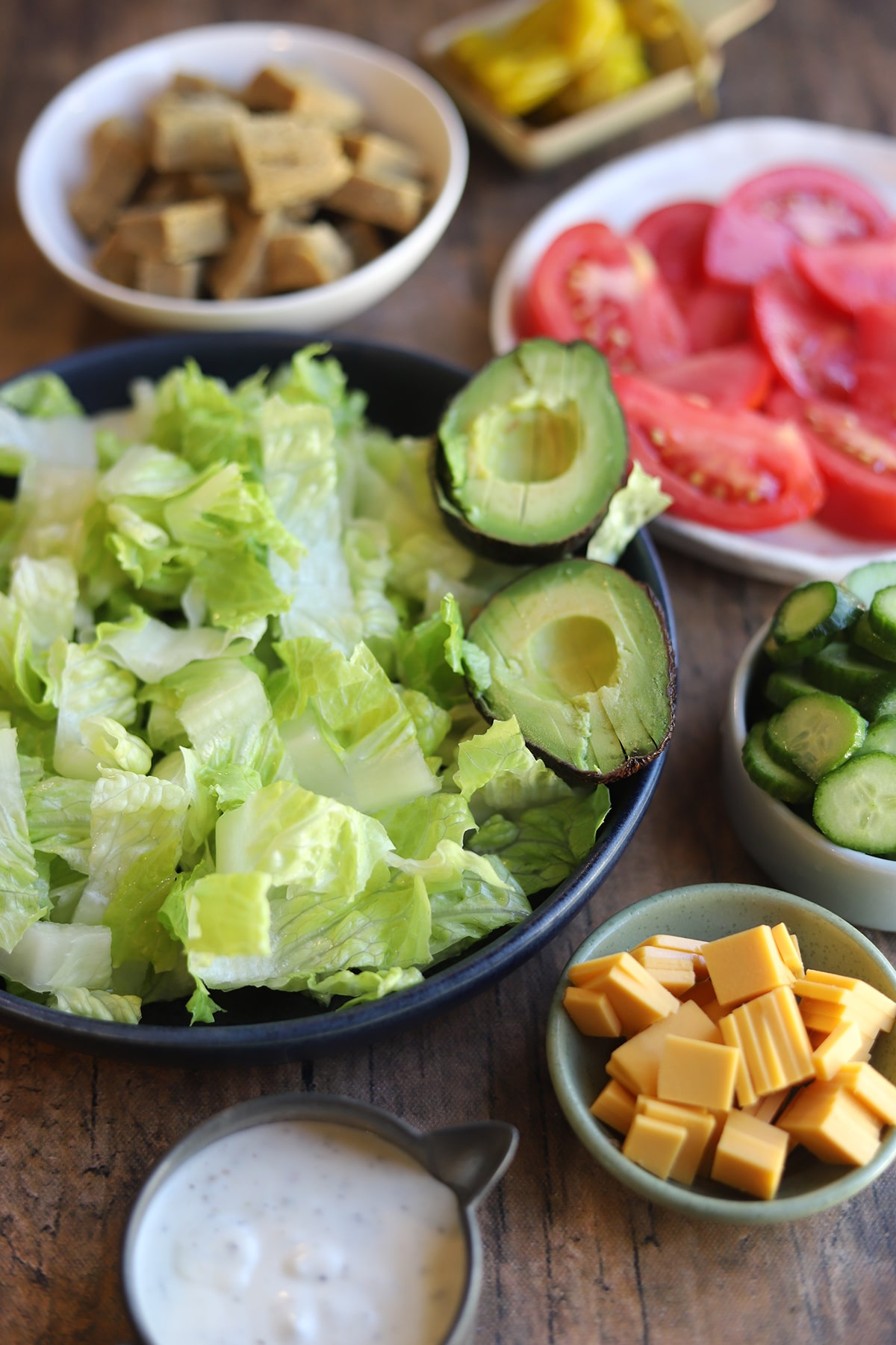 Bowl of lettuce with halved avocado, seitan, cheese, and dressing on table.