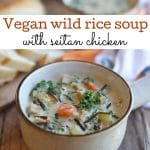 Text overlay: Vegan wild rice soup with seitan chicken. Bowl of soup on table by bread.